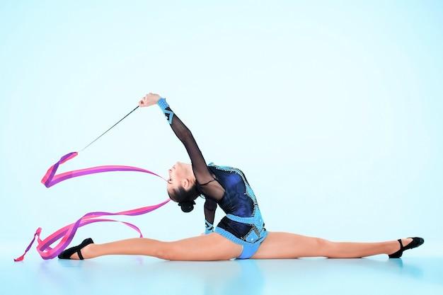 파란색 벽에 컬러 리본으로 체조 댄스를하는 소녀