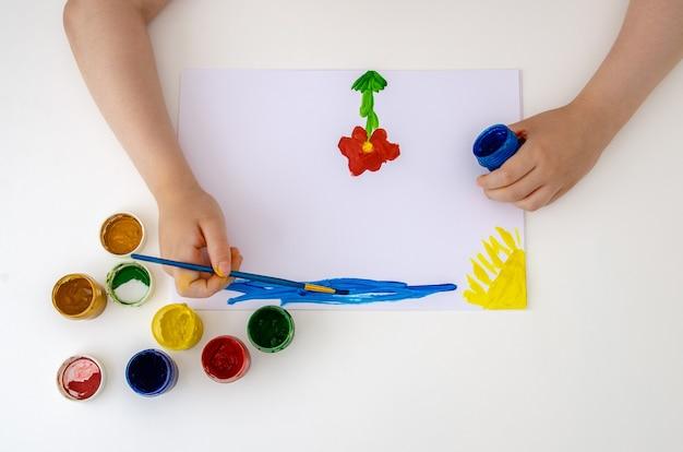 소녀는 도화지에 색 물감으로 꽃을 그립니다.