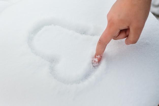 女の子は雪の上で指でハートを描きます。バレンタインデーおめでとうございます_