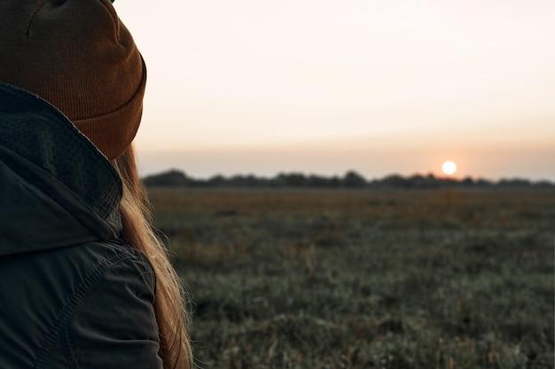 女の子はカップから飲み、冷たい夜明けを見ます。旅行。