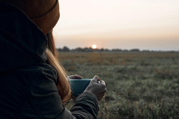 소녀는 컵에서 술을 마시고 추운 새벽을 바라본다. 여행기.