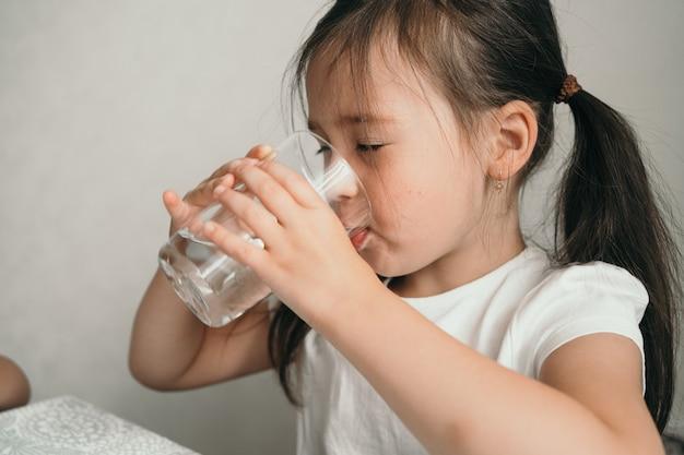 女の子はガラスガラスから水を飲みます小さな女の子は子供のための彼女の喉の渇きの適切な栄養を癒します...