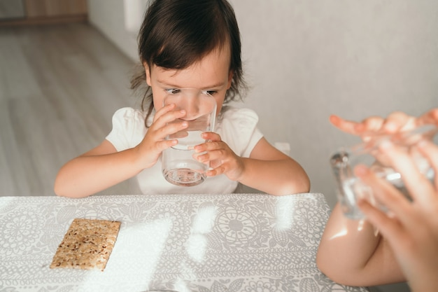 소녀는 유리잔으로 물을 마신다. 어린 소녀는 갈증을 해소합니다. 어린이를 위한 적절한 영양. 아이들의 오후 간식으로 간식. 고품질 사진