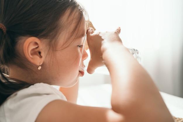女の子はガラスのグラスから水を飲みます。小さな女の子が喉の渇きを癒します