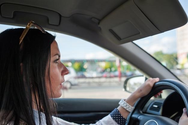 女の子は車を注意深く運転する。回すときは注意してください。舌を抜いた新しい車に座っている美しいブロンドの女の子。運転注意。