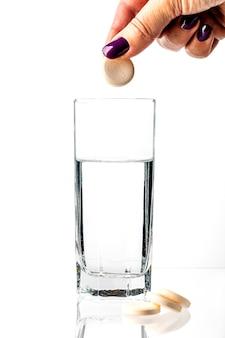 소녀는 큰 흰색 알약을 물 한잔에 떨어 뜨립니다.