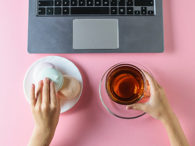 여자는 테이블에 컴퓨터 앞에서 차와 함께 블루 마시멜로를 먹는다