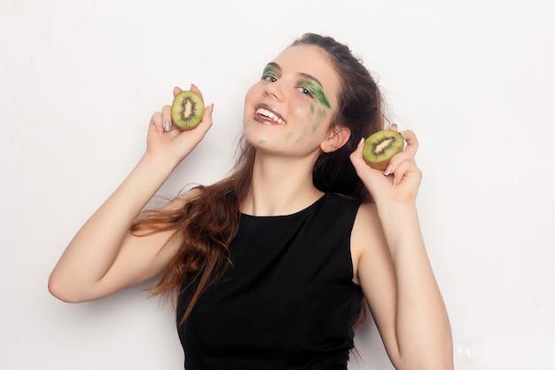 그 소녀는 반 키위를 먹습니다. 행복한 젊고 황홀한 아름다운 젊은 여성이 실내에서 재미있는 농담이나 역동적인 비타민 c를 위해 두 개의 자른 키위를 눈에 들고 있습니다.