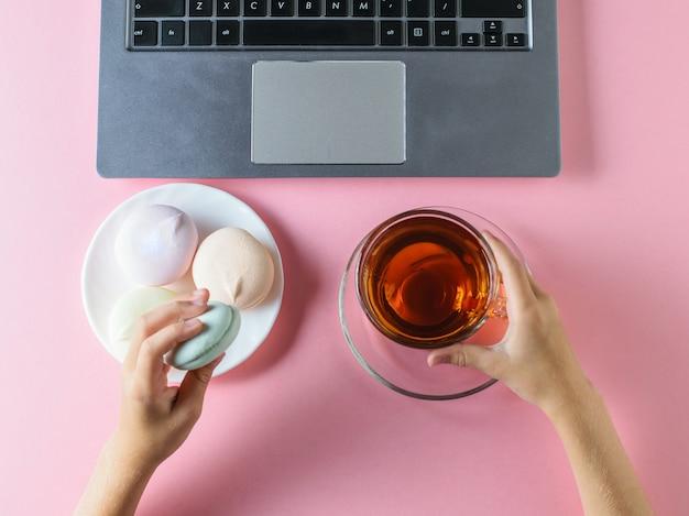女の子は色付きのマシュマロを食べ、ピンクのテーブルのコンピューターの近くでお茶を飲みます。上からの眺め。
