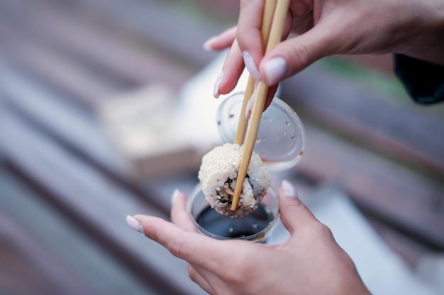 女の子はベンチで醤油と箸で寿司を食べます。シーフードデリバリーのコンセプト。