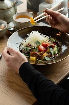 女の子は箸で、鶏肉、にんじん、焼きトウモロコシ、チーズ、チェリートマトのスパイシーなアジア野菜サラダを食べます。浅い被写界深度、ぼやけた背景