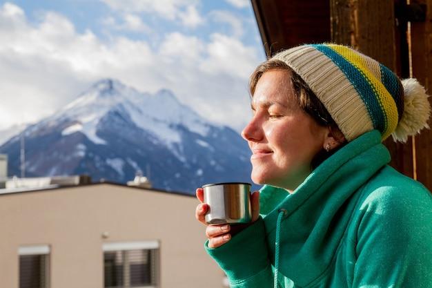Девушка наслаждается своим напитком и смотрит на горы