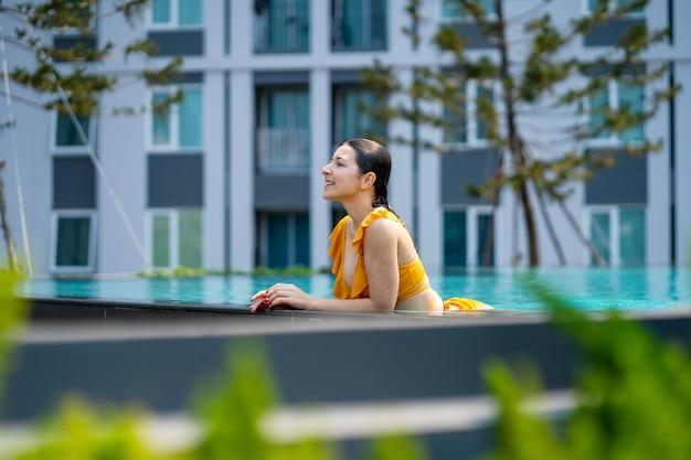 女の子は暑い夏の日にプールでリラックスするのを楽しんでいます。都市の住宅団地のプール。