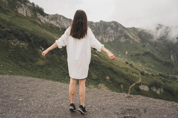 소녀는 산의 아름다움과 장엄함을 즐긴다 흰 셔츠를 입은 남자가 등을 대고 서있다 ...