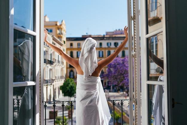Девушка с энтузиазмом распахнула двери балкона и смотрит вдаль на город. вид со спины