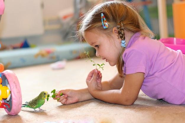 Девочка кормит попугая свежей травой зеленый волнистый попугайчик Premium Фотографии