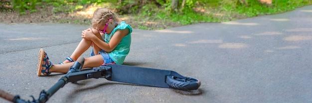 少女は公園でスクーターに乗っているときに転倒し、ひざをひどく傷つけた。電動スクーター傷害の概念。テキストの場所を含むパノラマ写真