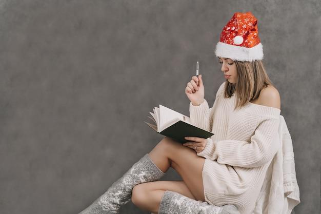 女の子は日記に記入します。人は思考の力を実践します。新年をお祈りします。友達や家族へのプレゼントのリストを作成します