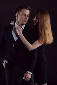 Девушка заигрывает с мужчиной и, глядя ему в глаза, расстегивает рубашку.