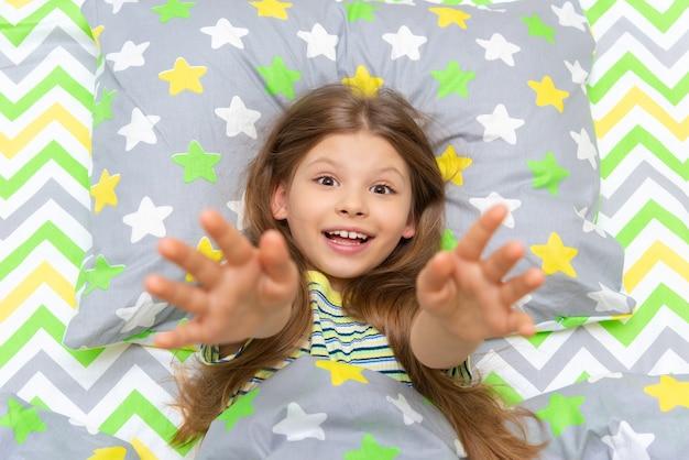 소녀는 침대에서 일어나고, 아이는 아침에 침대에서 기지개를 켠다.