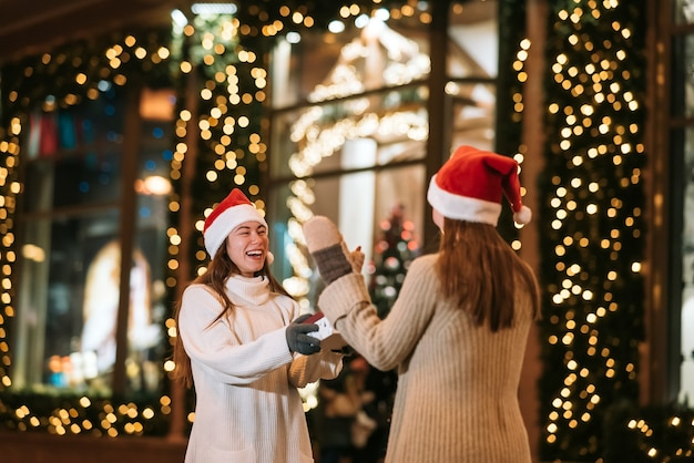 소녀는 길거리에서 그녀의 여자 친구에게 선물을 준다. 행복 한 귀여운 젊은 친구의 초상화