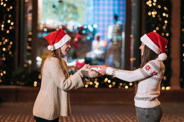 소녀는 길거리에서 그녀의 여자 친구에게 선물을 준다