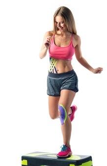 Девушка занимается спортом, к животу и коленям приклеены кинези-ленты.