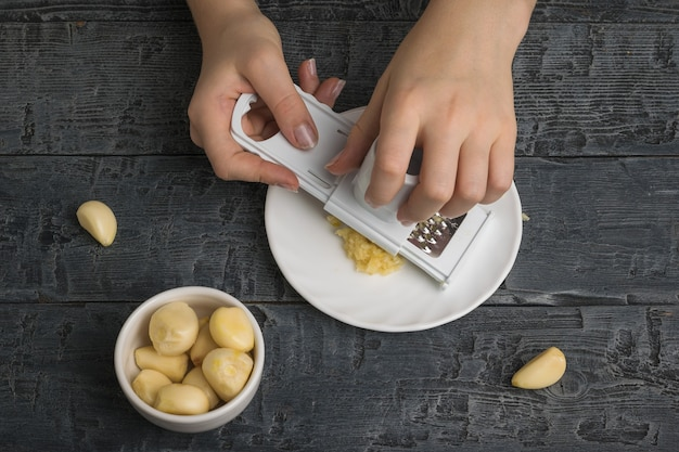 女の子は特別なおろし金で新鮮なニンニクを挽く。キッチンに人気のスパイス。