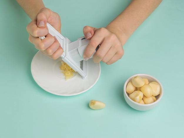 少女はおろし金でにんにくを挽く。キッチンに人気のスパイス。