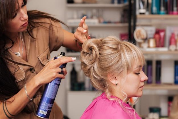 Девушка-парикмахер делает клиентке прическу на торжество. парикмахер все исправляет лаком для волос Premium Фотографии