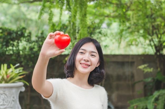 Девушка рука показывает мини красное сердце и улыбается, концепция любви