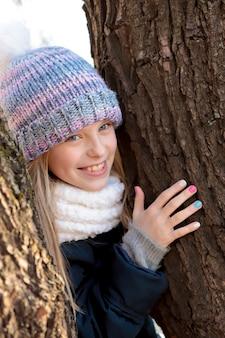 美しいマニキュアで木の周りに腕を組んで幸せそうに笑っている女の子。
