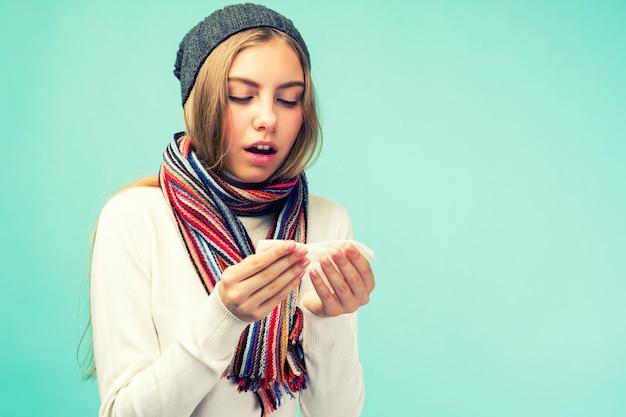 その少女はコロナウイルスの症状を持っています。健康と医学の概念-青い空間で、組織に鼻を吹く悲しい十代の少女。鼻水で冷たいかわいい女の子。