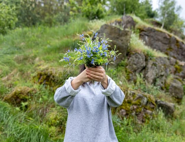 Девушка прячет лицо за букетом живых цветов, собранных в лесу.