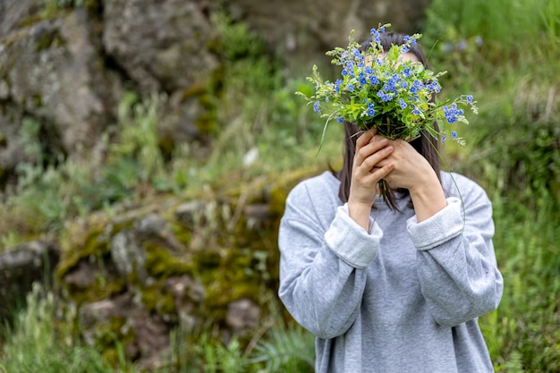 少女は森に集められた生花の花束の後ろに顔を隠します