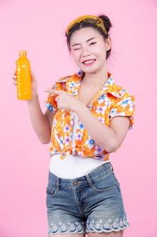 여자는 분홍색 배경에 오렌지 주스 한 병을 보유하고있다.
