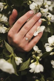 Девушка держит букет цветов, в руке обручальное кольцо, фото большого плана. французский маникюр на руку