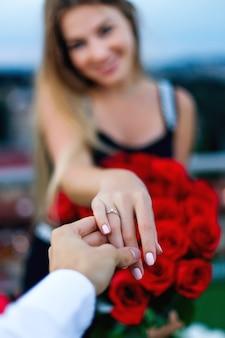 女の子は花束を持って、男に薬指に金の指輪を渡します