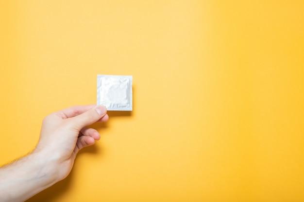 女の子は手にコンドームを持っています。黄色の壁、テキストのための場所。