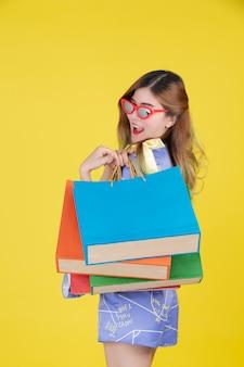 女の子はファッションショッピングバッグを保持し、黄色の背景にスマートカードを保持しています。