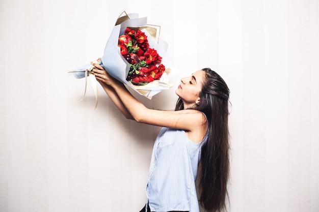 Девушка держит букет фруктов и поднимает его.