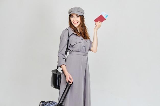 Девушка держит паспорт с билетами на самолет и выходит на посадку с багажом.