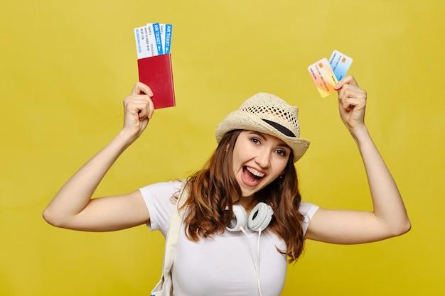 Девушка держит паспорт с билетами и кредитными карточками банка на желтом фоне.