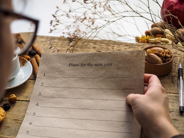 少女は新年の計画を書いた紙を手に持っています。