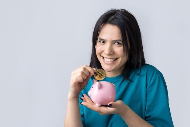 소녀는 분홍색 돼지 저금통과 동전을 손에 들고 있습니다. 부와 축적의 개념입니다.