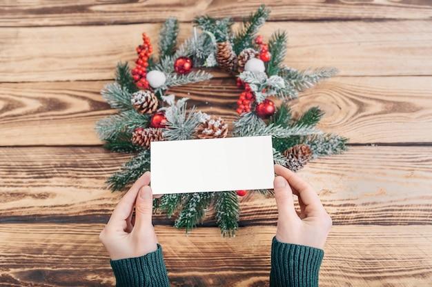 Девушка держит открытку на фоне рождественского венка и деревянного стола. макет. место для вставки.