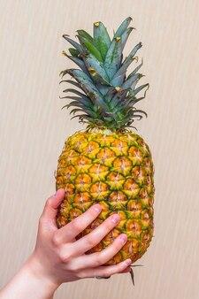 女の子は熟したおいしいパイナップルを手に持っています