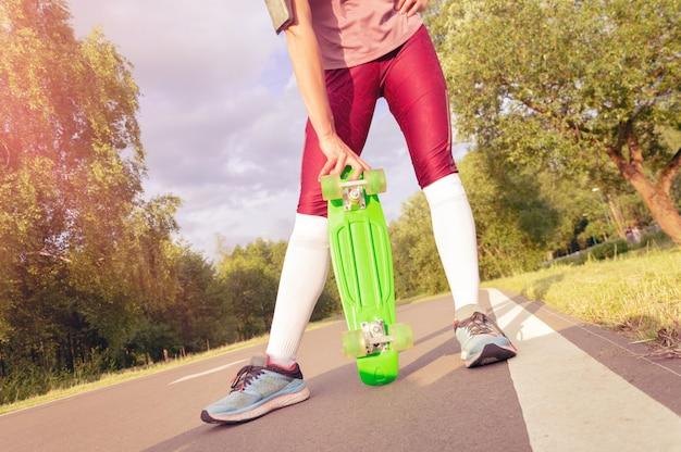 女の子はスケートボードを手に持っています。公園で追跡します。スポーツのコンセプト。ミクストメディア