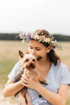 그 소녀는 여름에 자연 속에서 작은 yorkie 개를 안고 있습니다. 어린이 및 애완 동물.