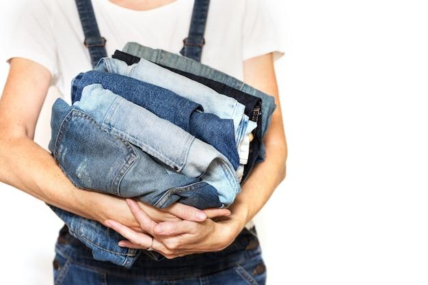Девушка держит в руках стопку джинсов. уборка в туалете.